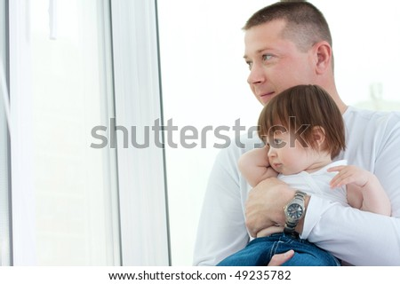 young father and her little beautiful daughter sitting at the window - stock photo