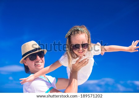 Young father and his adorable little daughter have fun at tropical beach vacation - stock photo