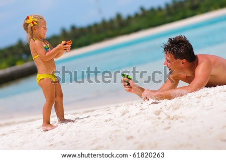young father and his cute daughter playing with water guns on exotic beach - stock photo