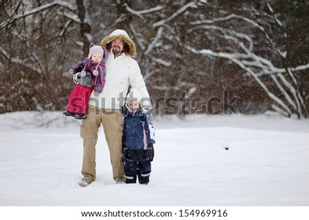 Young father and his daughters having fun on winter day