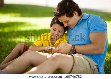 Young father and his son playing games on a cell phone while relaxing in a park - stock photo