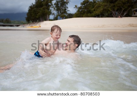 Young father and his son playing in the ocean - stock photo
