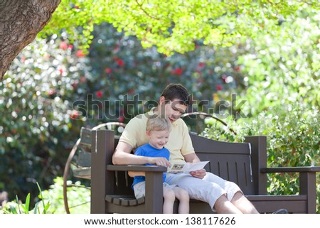 young father and his son sitting and exploring the map - stock photo