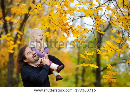 Young father and his toddler girl have fun at autumn - stock photo