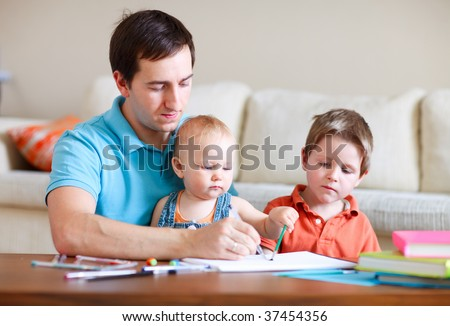 Young father and his two kids drawing together - stock photo
