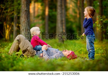 Young father and his two little daughters in forest - stock photo