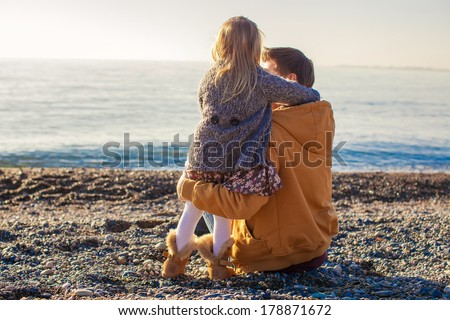 Young father and little girl at the beach on a sunny winter day - stock photo