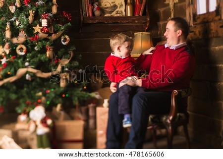 Young father and little son sitting in chair and playing in front of Christmas tree and presents. Christmas and New Year time celebration