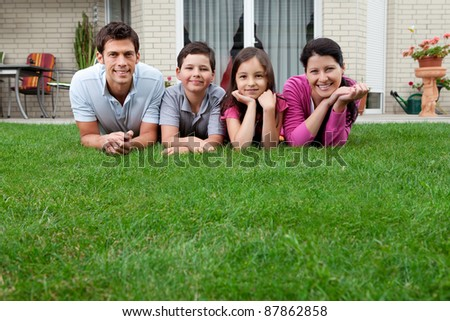 Young father and mother with their kids lying on grass in their backyard - stock photo