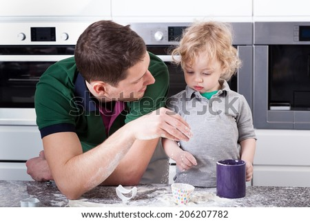 Young father and son baking muffins together