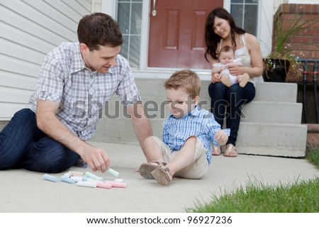 Young Father And Son Drawing With Chalk And Mother Sitting With Baby At Background In Front Of Their House. - stock photo