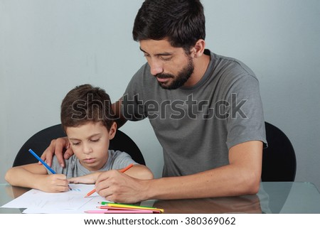 Young father and son drawing with colored pencils on the living room table