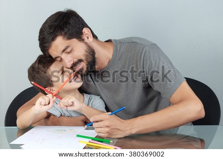 Young father and son embrace each other while drawing with colored pencils on the living room table - stock photo