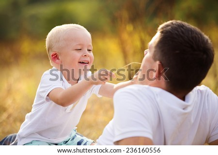 Young father and son enjoying life together. They are playing outside in nature - stock photo