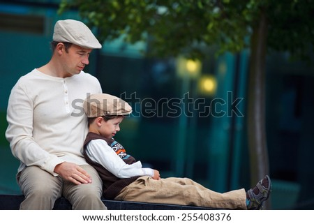 Young father and son having rest outdoors in city on beautiful summer day - stock photo
