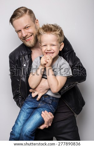 Young father and son playing together. Fathers day. Studio portrait over white background  - stock photo