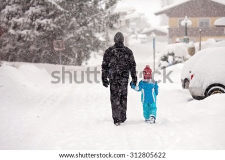 Young father and son, walking hand in hand down the street on a snowy day - stock photo