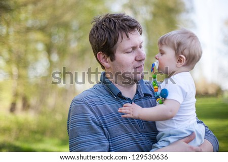 Young father and sweet baby boy in spring forest on sunny warm day