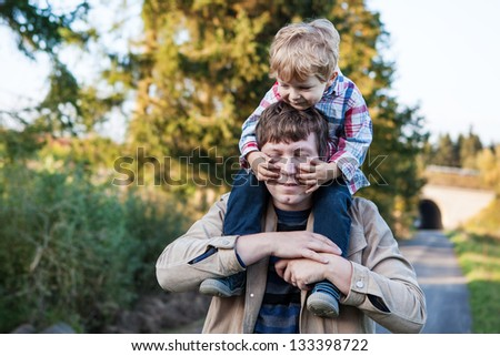 Young father and toddler walking in summer forest landscape, Germany.