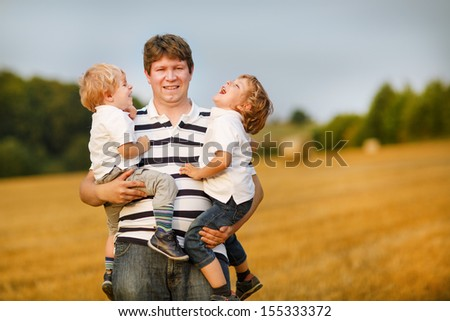 Young father and two little sibling boys having fun on yellow hay field in summer - stock photo
