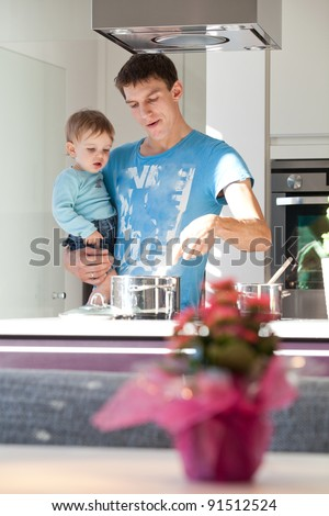 Young father cooking with his baby son in a modern kitchen. - stock photo