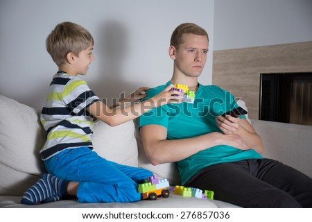 Young father don't pay attention to his son - stock photo
