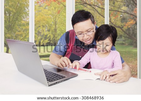 Young father helps his daughter studying and doing homework with a book and laptop on the table at home
