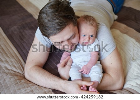 Young father holding his newborn baby son - stock photo