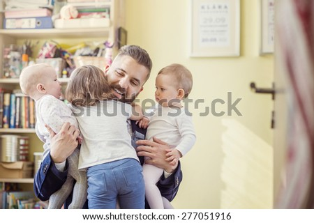 Young father hugging his daughters as he gets home from work - stock photo