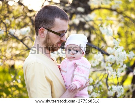 Young father in glasses with his little daughter in his arms, selective focus - stock photo
