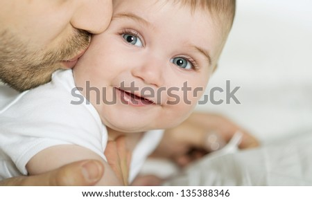 Young father is playing with his baby - stock photo