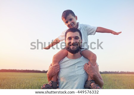 Young father is walking with his small son on shoulders in the field during sunset