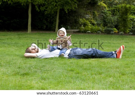 Young father lying in grass with a baby sitting on his belly - stock photo