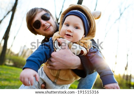 Young father playing on his son - stock photo
