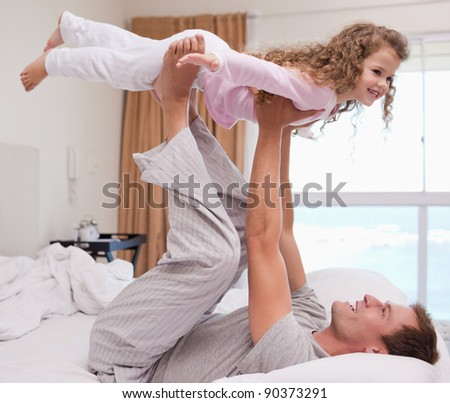 Young father playing plane with his daughter