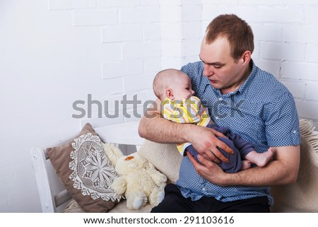 young father playing with his newborn baby - stock photo
