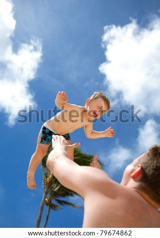 Young father playing with his son on a tropical beach - stock photo