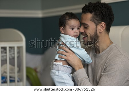 Young father sitting on his bed, holding his baby son. He has his nose pressed to his son's cheek. - stock photo
