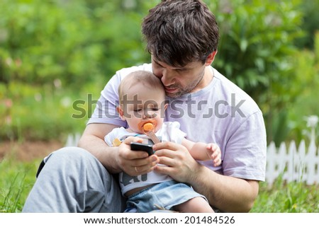 Young father sitting on the grass in the garden holding a newborn baby on his lap and texting on his mobile phone