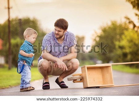 Young father talking with his little son on street - stock photo