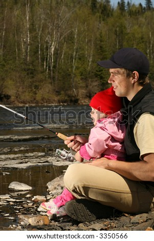 young father teaching his excited little daughter to fish in a rocky river - stock photo