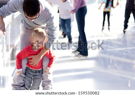 young father teaching his little smiling son ice skating and having fun time - stock photo