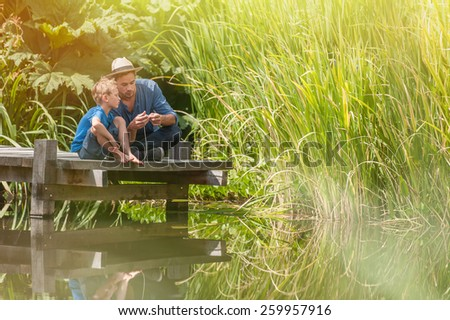 young father teaching his son to make a fishing rod, they are sitting on a wood pontoon on a river - stock photo
