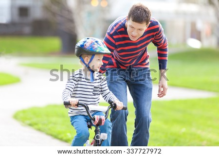 young father teaching his son to ride the bike in the park - stock photo