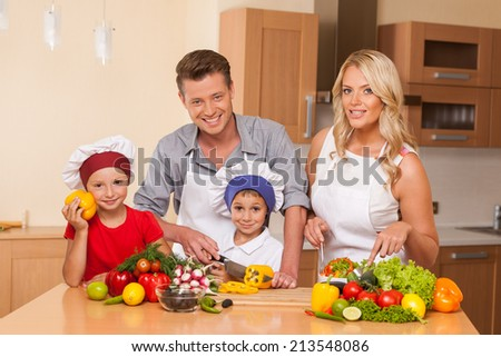 Young father teaching son how to prepare salad. boy and girl helping with food at kitchen - stock photo