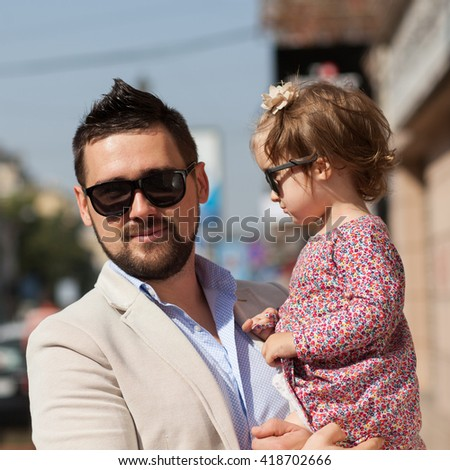 Young father walking with tiny daughter - stock photo