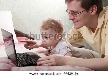 Young father with her little baby daughter with laptop