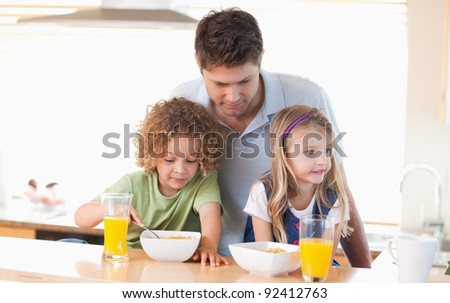 Young father with his children having breakfast in their kitchen - stock photo
