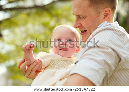Young father with his infant daughter outdoors - stock photo