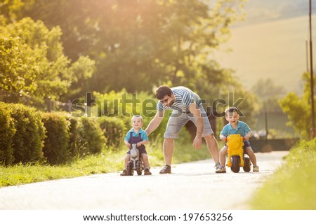 Young father with his little sons on motorbikes in green sunny park - stock photo
